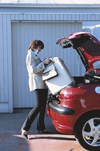 スーツケースを車のトランクに入れる女性の写真素材 [FYI03232637]