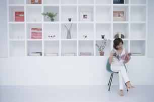棚の前に座って雑誌を読む女性の写真素材 [FYI03232639]
