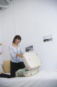 白いスーツケースに荷造りする女性の写真素材 [FYI03232643]