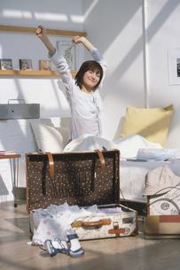 旅行鞄と伸びをする寝起きの女性の写真素材 [FYI03232646]
