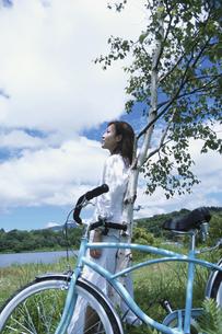 木に寄りかかり休憩する女性の写真素材 [FYI03232666]