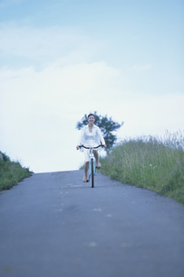 自転車で坂を下る女性の写真素材 [FYI03232669]