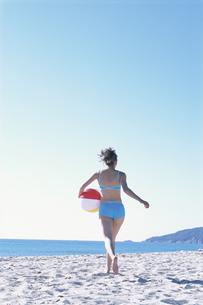 ビーチボールを持って走る水着の女性の写真素材 [FYI03232709]