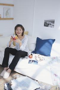 ソファに座ってノートをめくる女性の写真素材 [FYI03232715]