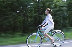 自転車で林の前の道を走る女性の写真素材 [FYI03232728]