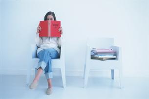 椅子に座り本を広げる女性の写真素材 [FYI03232758]