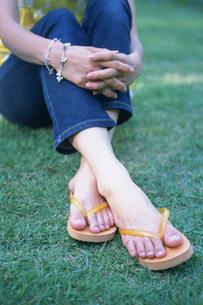 芝生に座るサンダルを履いた女性の写真素材 [FYI03232814]