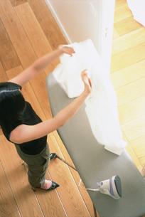 シャツにアイロンをかける女性の写真素材 [FYI03232833]