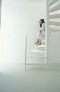 白い螺旋階段に座る外国人女性の写真素材 [FYI03232841]