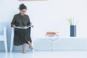 壁際の椅子に座り本を読む女性の写真素材 [FYI03232878]
