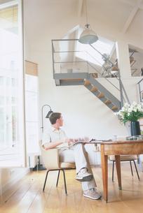 椅子に座る男性とロフトに続く階段の写真素材 [FYI03232885]
