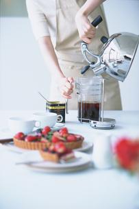 紅茶を入れる女性とフルーツタルトの写真素材 [FYI03232939]