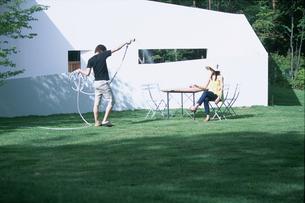 芝に水撒きをする男性と座る女性の写真素材 [FYI03233003]