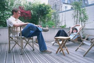 ウッドテラスの椅子で寛ぐカップルの写真素材 [FYI03233007]