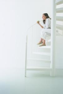白い螺旋階段に座る女性の写真素材 [FYI03233033]