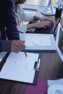 スケジュールチェックをする男性とパソコンを打つ女性の写真素材 [FYI03233542]