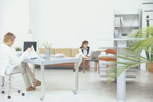 デスクに座る男性とソファの女性の写真素材 [FYI03233902]