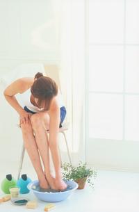 椅子に座ってフットケアをする女性の写真素材 [FYI03233922]