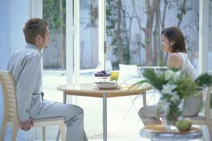 テーブルを挟んで会話するカップルの写真素材 [FYI03233944]