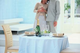 シャンパンのあるテーブルとカップルの写真素材 [FYI03233947]