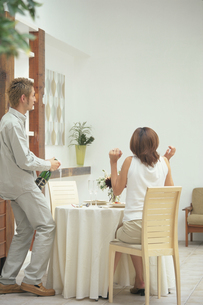 ボトルを開ける男性と座った女性の写真素材 [FYI03233948]