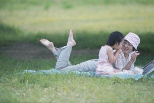 公園で寝そべって戯れる母と子の写真素材 [FYI03234038]