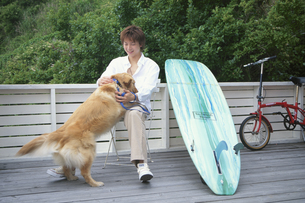 犬と戯れる男性とサーフボードの写真素材 [FYI03234074]