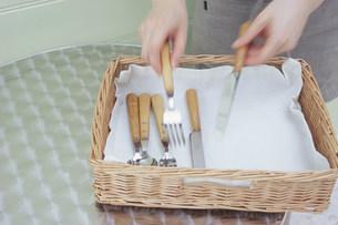 ラタンのトレーに食器を並べる手の写真素材 [FYI03234138]