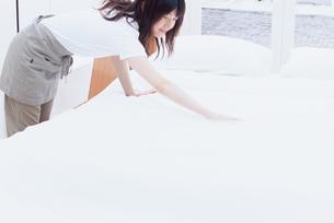 シーツを整える女性の写真素材 [FYI03234139]