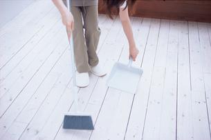 床のゴミを掃き集める人の足元の写真素材 [FYI03234142]