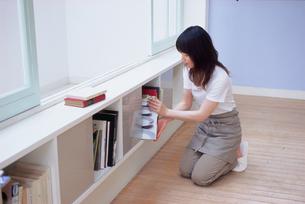 本棚を整理する女性の写真素材 [FYI03234168]