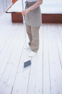 箒で掃除をする女性の写真素材 [FYI03234198]