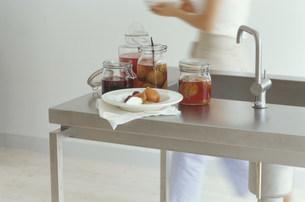 シンクに置かれたフルーツの瓶詰めと女性の写真素材 [FYI03235115]