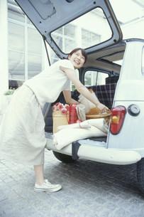 車の荷台から荷物を出す日本人女性の写真素材 [FYI03235255]