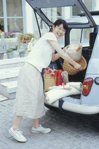 車の荷台から荷物を出す日本人女性の写真素材 [FYI03235263]