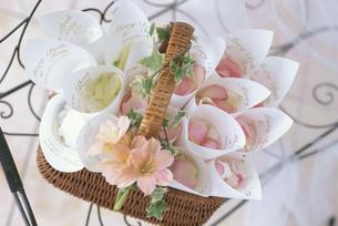 椅子の上に置いた花びらの入ったバスケットの写真素材 [FYI03235302]