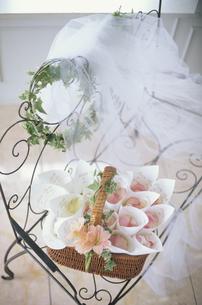 ワイヤー長椅子の上に花びらの入ったバスケットの写真素材 [FYI03235313]