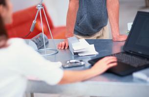 デスクについた男性の腕とノートパソコンにふれる打つ女性の写真素材 [FYI03235623]