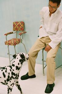 椅子に座った男性とダルメシアンの写真素材 [FYI03235637]