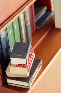 木製の本棚に重ねておいた洋書の写真素材 [FYI03235702]