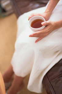 白スカートの女性が膝元に持ったお茶の写真素材 [FYI03235724]
