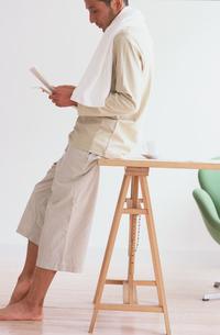 部屋着でデスクに腰掛けた男性の写真素材 [FYI03235734]