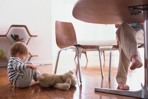 男性の足元で床に座る外人子供の写真素材 [FYI03235741]