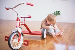 赤い三輪車と外国人男の子の写真素材 [FYI03235743]