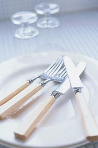 白いお皿の上のカトラリーと脇のグラスの写真素材 [FYI03235776]