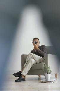 イスに座りカメラを構える男性の写真素材 [FYI03235795]