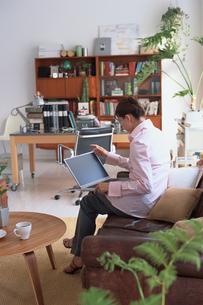 リビングでノートパソコンを開ける女性の写真素材 [FYI03235835]
