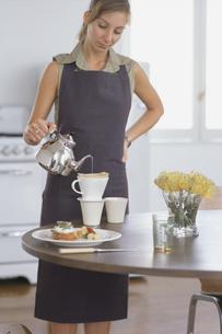 テーブルでコーヒーを注ぐ女性の写真素材 [FYI03235844]
