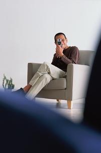 ソファに座ってカメラを覗く男性の写真素材 [FYI03235857]
