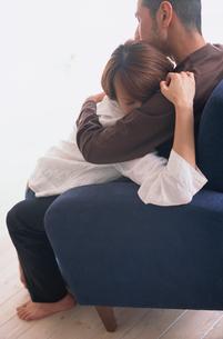 青いソファで抱き合うカップルの写真素材 [FYI03235862]